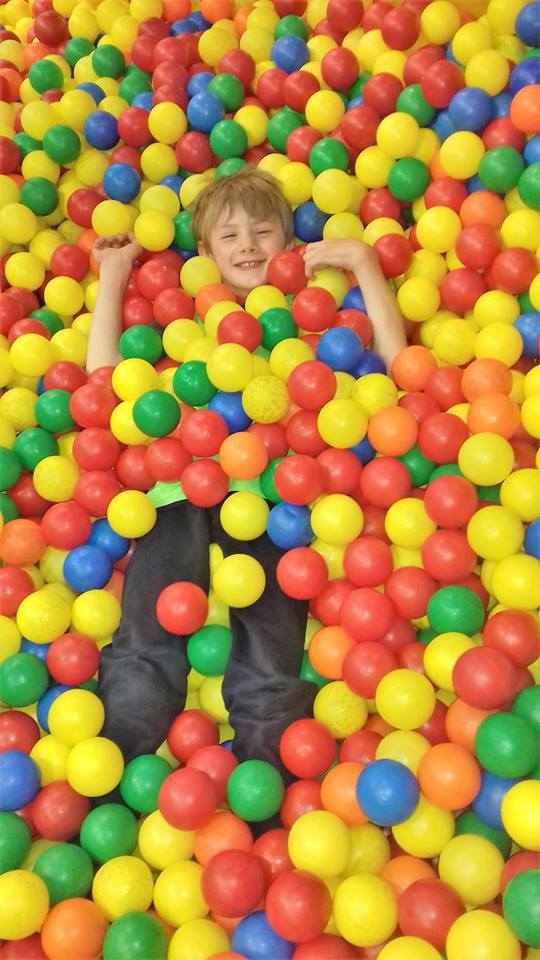 Image shows child playing in colourful ball pool smiling.